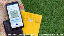 Ein Sonnenhut mit einem Reisepass, Impfbuch und digitalem Impfzertifikat auf einem Mobiltelefon. (Themenbild, Symbolbild, Model Release, Geänderte QR-Code)