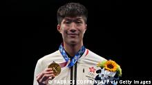 Gold medallist Hong Kong's Cheung Ka Long celebrates on podium during the medal ceremony for the mens individual foil during the Tokyo 2020 Olympic Games at the Makuhari Messe Hall in Chiba City, Chiba Prefecture, Japan, on July 26, 2021. (Photo by Fabrice COFFRINI / AFP) (Photo by FABRICE COFFRINI/AFP via Getty Images)
