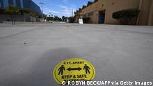 A social distance sign is taped to the ground at a Covid-19 vaccination center offering the Pfizer vaccine to anyone over the age of 12 who wants it, at Crenshaw High School in the traditionally Black and Latino neighborhood of South Los Angeles on July 8, 2021. - The clinic was empty except for the staff working there. Covid cases are rising rapidly in the United States as the Authorities are working to educate vaccine hesitant populations of the value, efficacy and safety of the Covid vaccines to prevent the spread of the Delta variant. (Photo by Robyn Beck / AFP) (Photo by ROBYN BECK/AFP via Getty Images)