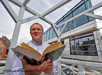 Codiretor Ralf Eichberg folheia um dos 7 mil volumes do acervo