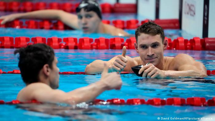 Ryan Murphy, right, gives a thumbs up to Evgeny Rylov in the pool