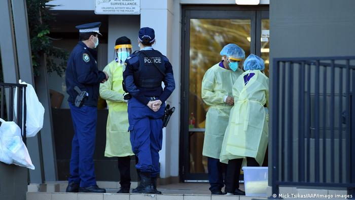 Sydney police officers speak with health workers at a locked down building where positive cases have been detected