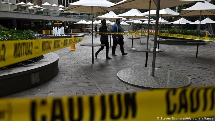 A man walks past caution tape blocking an eating area during lockdown in Sydney