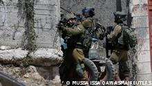 An Israeli army soldier aims his weapon during the funeral of 12-year-old Palestinian boy Mohammad Al Alami, who was killed by Israeli troops, according to the Palestinian health ministry, near Hebron in the Israeli-occupied West Bank July 29, 2021. REUTERS/Mussa Qawasma