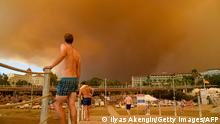 29/07/2021*** TOPSHOT - Dark smoke drifts over a hotel complex during a massive forest fire which engulfed a Mediterranean resort region on Turkey's southern coast near the town of Manavgat, on July 29, 2021. - At least three people were reported dead on July 29, 2021 and more than 100 injured as firefighters battled blazes engulfing a Mediterranean resort region on Turkey's southern coast. Officials also launched an investigation into suspicions that the fires that broke out Wednesday in four locations to the east of the tourist hotspot Antalya were the result of arson. (Photo by Ilyas AKENGIN / AFP) (Photo by ILYAS AKENGIN/AFP via Getty Images)