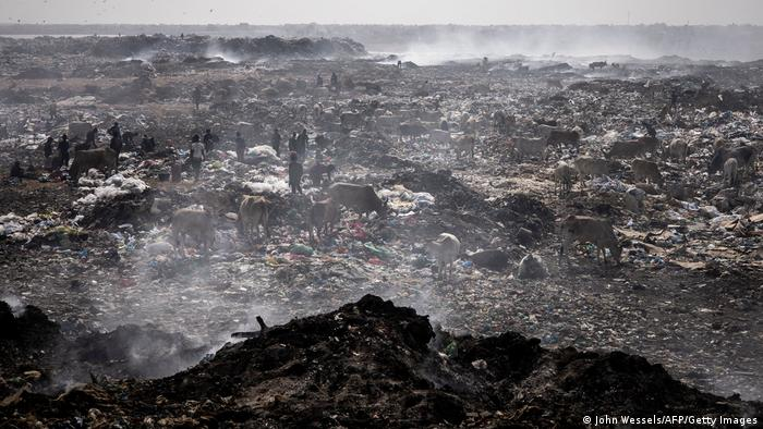 Waste pickers search of recyclable waste to sell in the Mbeubeuss rubbish dump in Dakar on July 14, 2021.