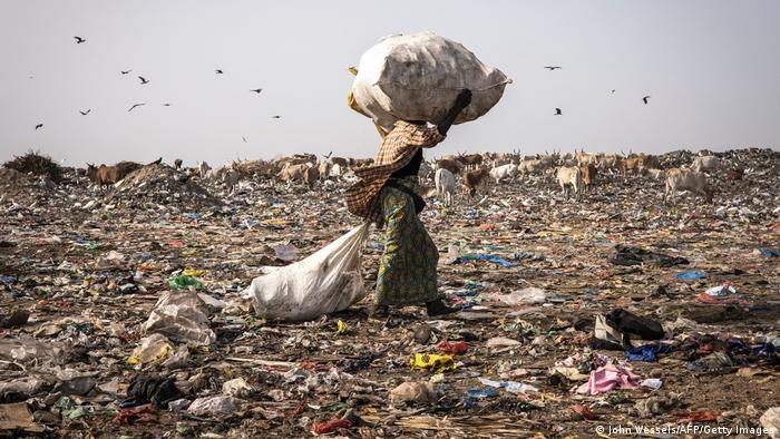 A waste picker walks with a load of recyclable waste on her head in the Mbeubeuss rubbish dump in Dakar.