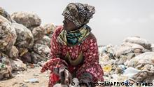 A woman ties her sack of recyclable waste in Dakar on July 14, 2021. - Almost all of it ends up in Mbeubeuss, a landfill about 30 kilometres (18 miles) from the centre which has a notorious reputation as an environmental hazard. Pickers set fire to the rubbish to find valuable metals, for example, spewing noxious fumes onto neighbouring residential areas. (Photo by JOHN WESSELS / AFP) (Photo by JOHN WESSELS/AFP via Getty Images)