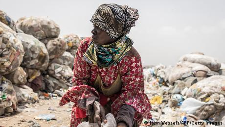 A woman ties her sack of recyclable waste in Dakar on July 14, 2021