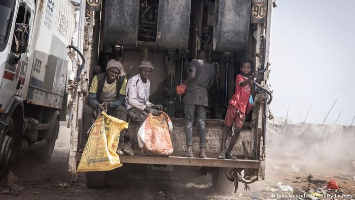 Young waste pickers catch a ride to the main rubbish mound in the Mbeubeuss rubbish dump in Dakar.