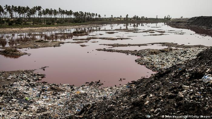 A lake has turned red from pollution is pictured on the outskirts of the Mbeubeuss rubbish dump.