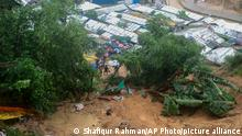 27.07.21 *** Rohingya refugees and others hold umbrellas as they search for survivors after a landslide triggered by heavy rains in a camp at Ukhiya in Cox's Bazar district, Bangladesh, Tuesday, July 27, 2021. (AP Photo/ Shafiqur Rahman)