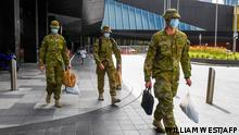 Soldiers walk from a hotel in Melbourne on December 7, 2020 where Australians returning from overseas will quarantine as part of precautions against the Covid-19 coronavirus. - An outbreak of the coronavirus from hotel quarantine earlier in the year from saw a second wave of infections and a suspension of arrivals until today. (Photo by William WEST / AFP)