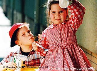Crianças mostram potinhos de iogurte que serão reciclados
