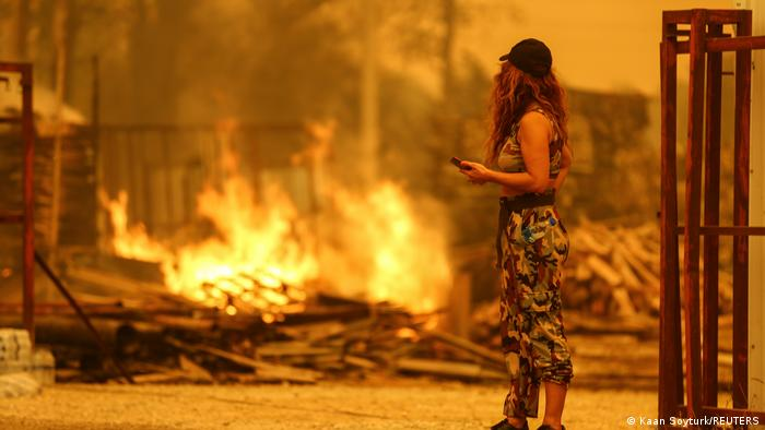 A woman stands next to a blaze that is burning some debris and has turned the whole picture orange