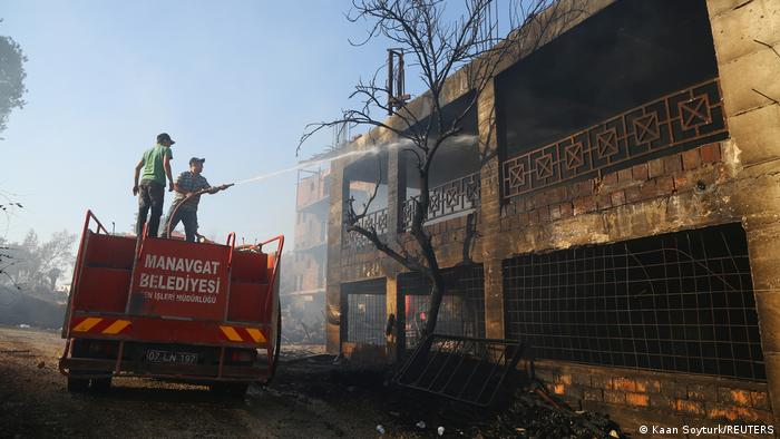 A firefighter cools a burnt house as a massive forest fire spread to the town of Manavgat