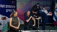 30.07.21 *** Israeli President Isaac Herzog receives a third coronavirus vaccine injection while his wife, Michal, left, reacts, at the Sheba Medical Center in Ramat Gan, Israel, Friday, July 30, 2021. (AP Photo/Maya Alleruzzo, Pool)