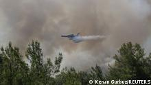 30.07.21 *** A firefighting aircraft drops water while extinguishing a forest fire near Marmaris, Turkey, July 30, 2021. REUTERS/Kenan Gurbuz