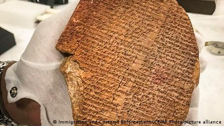 A gloved hand holding a tablet with a portion of the Epic of Gilgamesh that was looted from Iraq