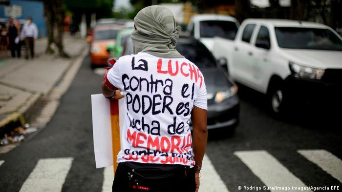 Foto de una persona que participa en una marcha para conmemorar la masacre de la UES en El Salvador.