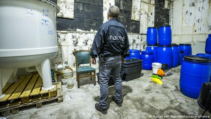A police officer investigates the site of a large drug lab in Nederweert, Netherlands