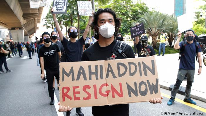 A protester holds a placard that reads Mahiaddin [Muhyiddin] resign now