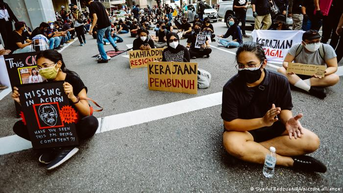 Youths carrying banners sit on a Kuala Lumpur street