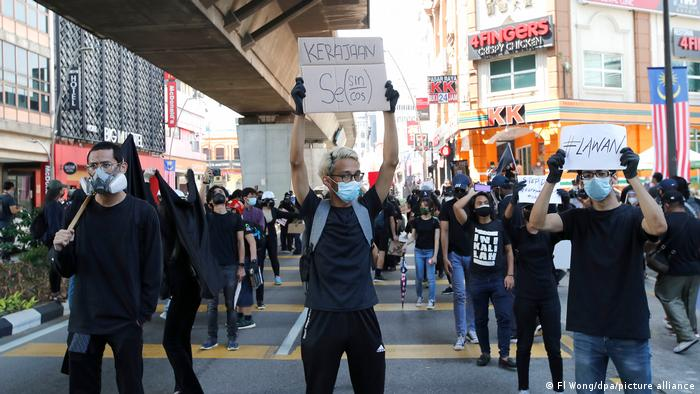 Malaysia protesters brandish signs demanding the government steps down
