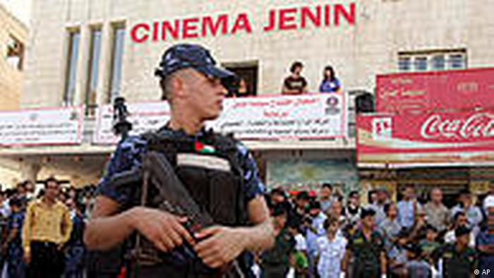A police officer stands guard as Palestinian gather for the opening of Cinema Jenin in the Palestinians West Bank city of Jenin, Thursday, Aug. 5, 2010. The Cinema was built by dozens of Palestinian and foreign volunteers and funded by half a million Euros from the German and Palestinian governments and Pink Floyd co-founder Roger Waters. The complex includes a 350-seat movie house, an outdoor cinema in the adjacent garden, a cafe, a guest house, a film library and a dubbing studio. (AP Photo/Mohammed Ballas)