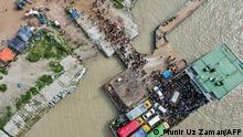 This aerial photograph taken on July 31, 2021 shows people disembark from a ferry in Sreenagar to resume and return to their work areas post the Bangladesh government relaxed the lockdown norms for all export oriented factories which were earlier imposed to curb the spread of Covid-19 coronavirus. (Photo by Munir Uz zaman / AFP)