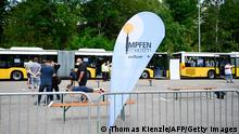 People line up next to banner reading vaccination protects in front of a mobile vaccination center against COVID-19 near the Mercedes-Benz arena in Stuttgart, southern Germany, on July 31, 2021 ahead of the football test match VfB Stuttgart v FC Barcelona. (Photo by THOMAS KIENZLE / AFP) (Photo by THOMAS KIENZLE/AFP /AFP via Getty Images)