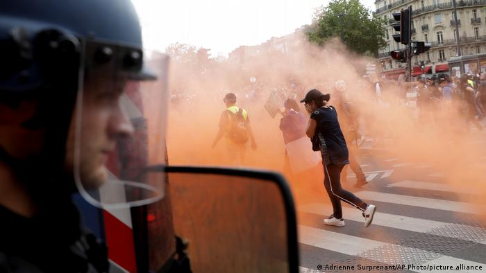 A French police officer in riot gear observes as protesters run through clouds of teargas
