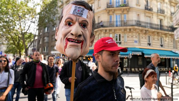 A young man wearing a Make America Great Again hat carries an effigy of French President Emmanuel Macron's head on a spike as he marches alongside other protesters in Paris