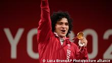 CORRECTS LAST NAME TO ELBAKH FROM ELBACH - Fares Elbakh of Qatar celebrates on the podium after winning the gold medal in the men's 96kg weightlifting event, at the 2020 Summer Olympics, Saturday, July 31, 2021, in Tokyo, Japan. (AP Photo/Luca Bruno)