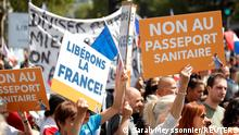 A protester holds a placard that reads No to the health passport during a demonstration called by the French nationalist party Les Patriotes (The Patriots) against France's restrictions, including a compulsory health pass, to fight the coronavirus disease (COVID-19) outbreak, in front of the Ministry of Health in Paris, France, July 31, 2021. REUTERS/Sarah Meyssonnier