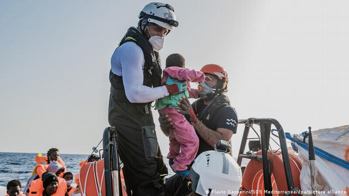 A rescuer with the Ocean Viking lifts up a child from a boat during a migrant rescue operation