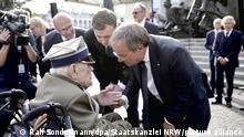 Armin Laschet, CDU/CSU-Kanzlerkandidat und Ministerpräsident von Nordrhein-Westfalen, spricht am Rande der Gedenkfeier an den Warschauer Aufstand mit einem Zeitzeugen. Laschet nahm am Samstagabend an einem Staatsakt und Gottesdienst am Denkmal des Warschauer Aufstands teil, der vor 77 Jahren ausbrach. +++ dpa-Bildfunk +++