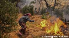 Eine Frau versucht mit einem Zweig ein Feuer auszuschlagen. Nachdem zwei Forstarbeiter bei Löscharbeiten in der südtürkischen Provinz Antalya ums Leben gekommen sind, stieg die Anzahl der Todesopfer auf sechs an. Seit dem 28.07.2021 wüten in der Türkei zahlreiche Waldbrände, wobei die türkische Mittelmeerküste besonders betroffen ist. +++ dpa-Bildfunk +++