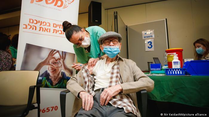 An elderly Israeli man receives his Pfizer vaccine