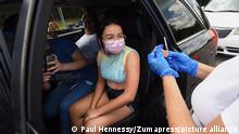 July 27, 2021, Orlando, United States: A nurse prepares to give 12 year-old Valeria Soto Serrano, a resident of Costa Rica, a shot of the Pfizer COVID-19 vaccine at a drive-thru vaccination and testing site at Barnett Park in Orlando. .Coronavirus cases in Orange County are currently reaching approximately 1,000 cases a day due to the Delta variant and high numbers of unvaccinated residents. (Credit Image: © Paul Hennessy/SOPA Images via ZUMA Press Wire