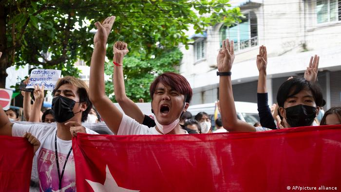 Protesters hold National League for Democracy (NLD) flags during protests against military rule in Yangon this June