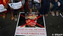 (FILES) In this file photo taken on February 11, 2021, protesters step on a banner showing an image of Myanmar military chief Senior General Min Aung Hlaing during a demonstration against the military coup in Yangon. - This August 1, 2021 marks six months since Aung San Suu Kyi, the daughter of independence hero Aung San, was detained in a coup by the military her father created, setting off a bloody crackdown that has killed hundreds. (Photo by STR / AFP) / TO GO WITH AFP STORY MYANMAR-POLITICS-MILITARY-ANNIVERSARY-COUP,FOCUS