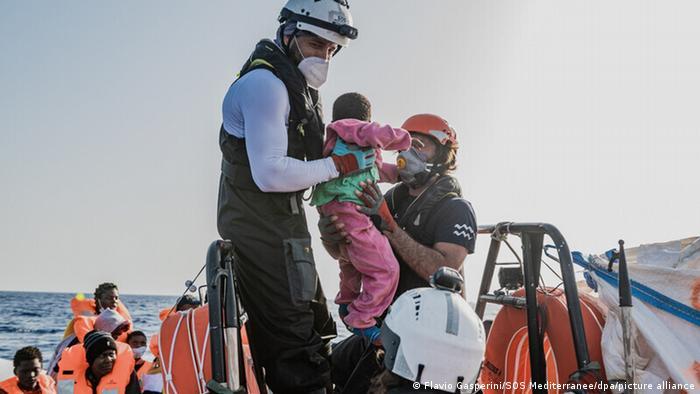 Ein Kleinkind wird von der Ocean Viking-Crew aus einem Schlauchboot gerettet
