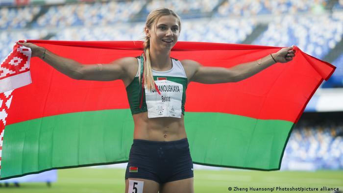 Krystsina Tsimanouskaya segura a bandeira de Belarus após vencer a provas dos 200 metros rasos na Universíade de 2019