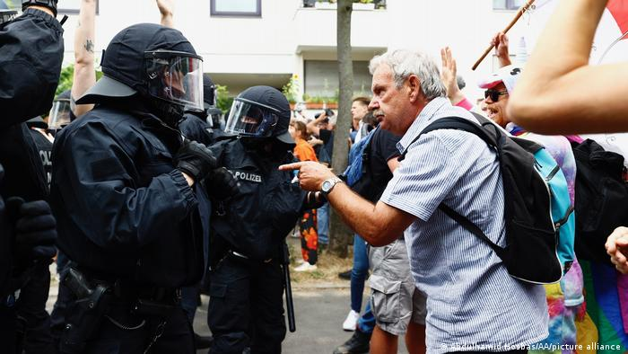 A protesting man points his finger at a police officer dressed in riot gear