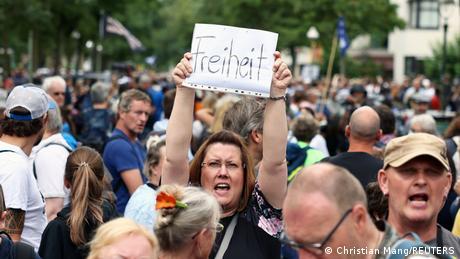 Une manifestante brandissant une feuille sur laquelle est écrit le mot liberté lors de la manifestation de Berlin.