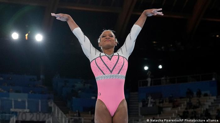 Rebeca de colant rosa e ebranco com brilhos, ergue os braços em apresentação.