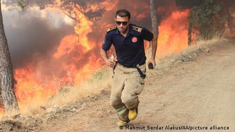 Bei den Waldbränden in der Türkei versucht ein Feuerwehrmann den Flammen zu entkommen.