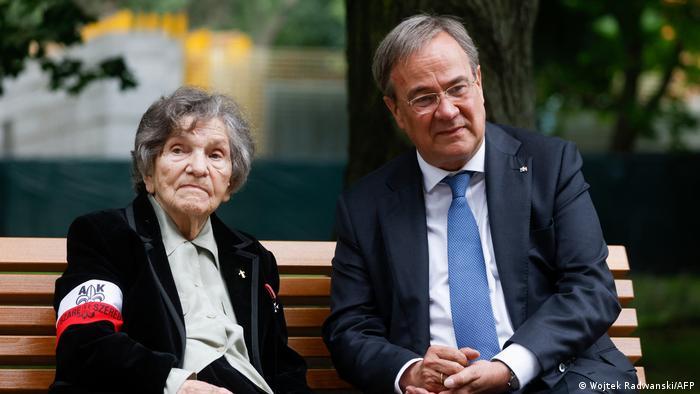 Laschet sits on a bench next to uprising veteran Wanda Traczyk-Stawska