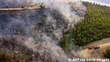 TOPSHOT - This aerial photograph shows firetrucks on a road as a wildfire which engulfed a Mediterranean resort region on Turkey's southern coast near the town of Manavgat, on July 30, 2021. - At least three people were reported dead on July 29, 2021 and more than 100 injured as firefighters battled blazes engulfing a Mediterranean resort region on Turkey's southern coast. Officials also launched an investigation into suspicions that the fires that broke out Wednesday in four locations to the east of the tourist hotspot Antalya were the result of arson. (Photo by - / AFP) (Photo by -/AFP via Getty Images)